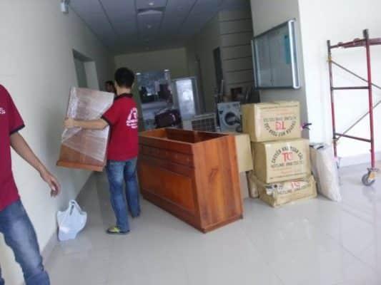Nhân viên Dịch Vụ Chuyển Nhà Trọn Gói đang vận chuyển đồ đạc thùng carton của khách
